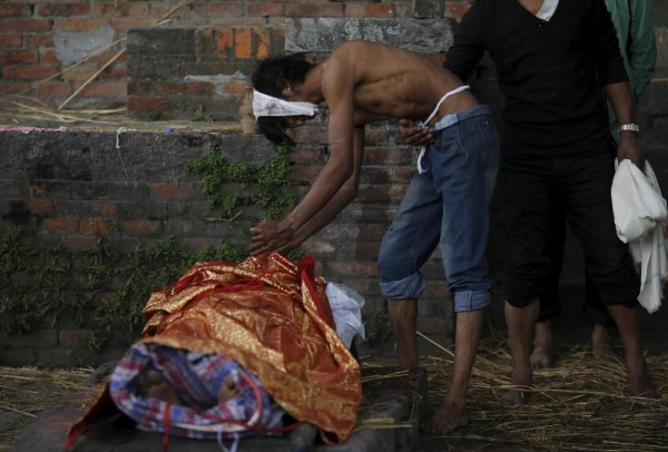 Boy cries over the body of his father at a cremation ground after an earthquake in Bhaktapur