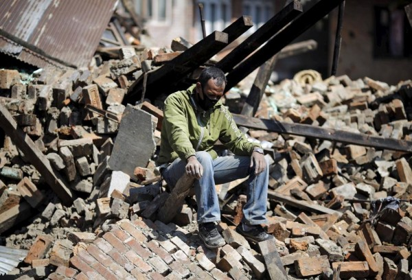Man sits on the rubble of his damaged house following Saturday's earthquake in Bhaktapur, Nepal