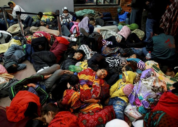 People sleep as they wait outside the departure terminal at the airport in Kathmandu