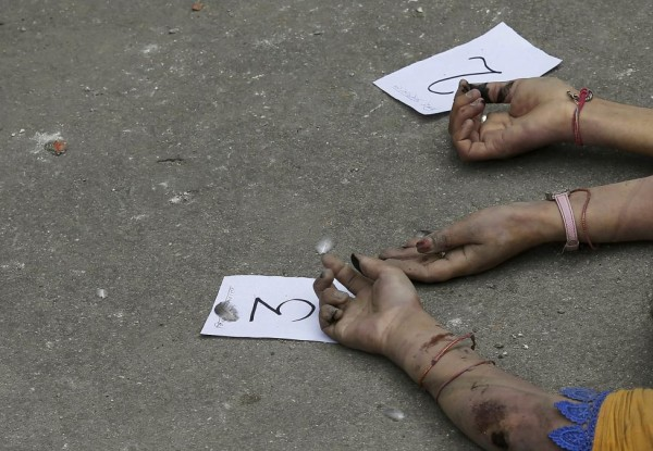 Identification numbers are seen next to dead bodies after an earthquake struck, outside a hospital in Kathmandu