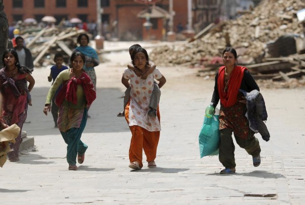 People rush for safety during a strong aftershock after an earthquake, in Kathmandu