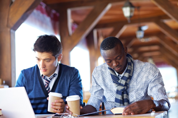 Two student friends sitting in cafe and learning