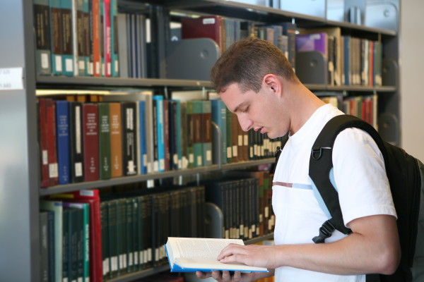 A college student reading a book in the library