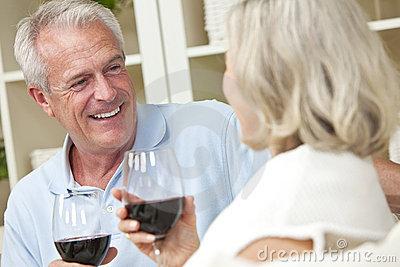 happy-senior-couple-drinking-wine-home-22855933