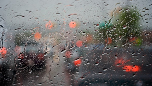 driving in the rain along Nose Hill Drive, traffic stopped at a red light.