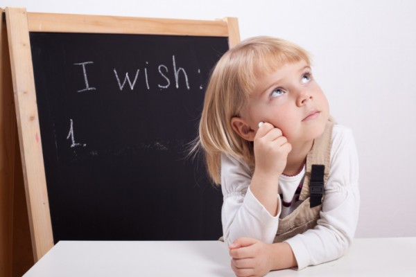little girl looking up with chalk thinking about wish list