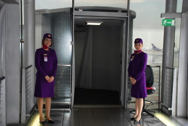 Why the cabin crew keep their arms behind their backs when greeting passengers