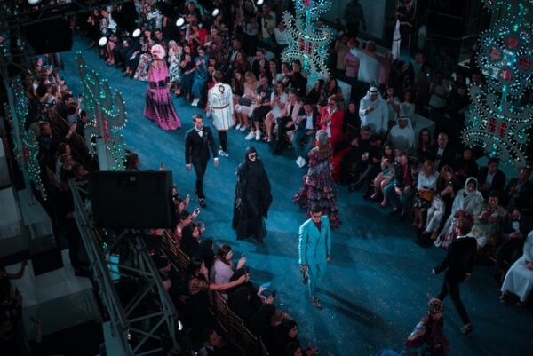 Models walking on a fashion show stage with the audience and lighted decorations lining the catwalk